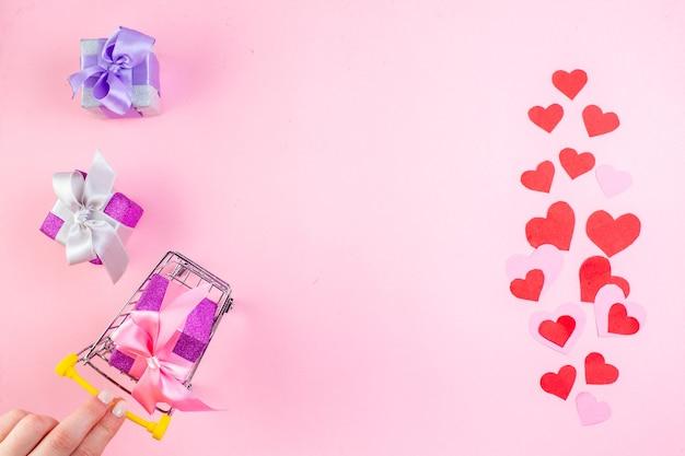 Vue de dessus petits cadeaux main féminine tenant un mini chariot de marché avec cadeau sur fond rose place de la copie