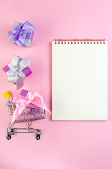 Vue de dessus petits cadeaux mini-marché bloc-notes chariot sur fond rose