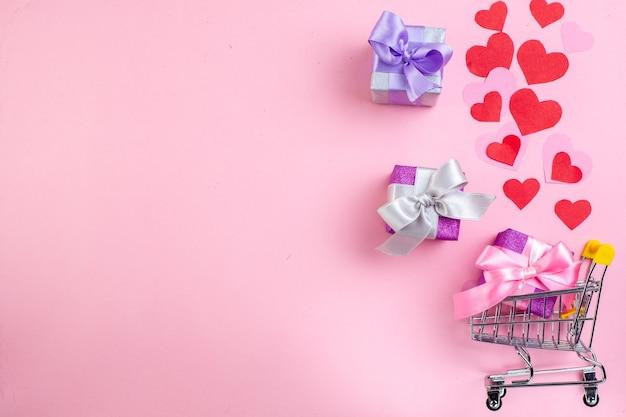 Vue de dessus petits cadeaux mini-marché chariot coeurs rouges sur fond rose avec copie place