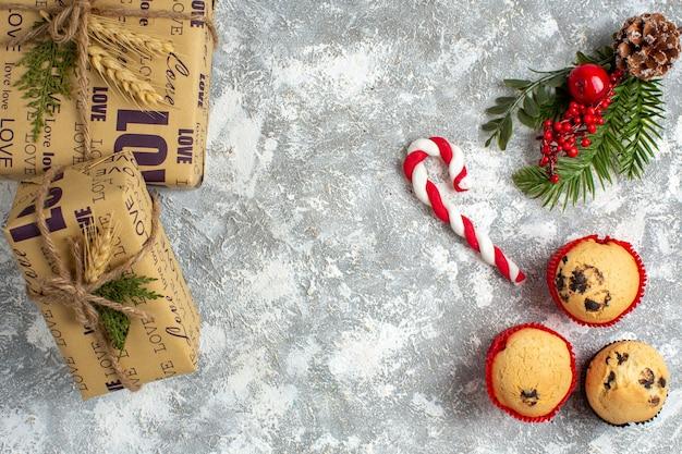 Vue de dessus de petits cupcakes bonbons et branches de sapin accessoires de décoration et cadeaux sur la surface de la glace