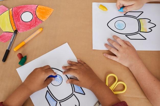 Vue de dessus petits enfants méconnaissables dessinant des images de fusées spatiales tout en profitant d'un cours d'art à l'école maternelle ou dans un centre de développement