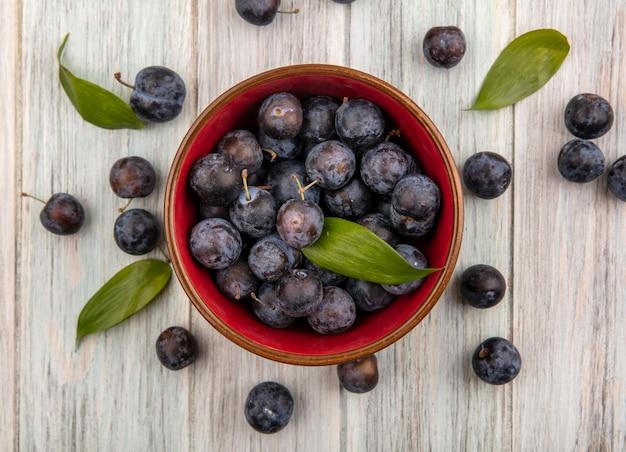 Vue de dessus de petits fruits violet foncé aigre prunelles sur un bol avec des prunelles isolé sur un fond en bois gris