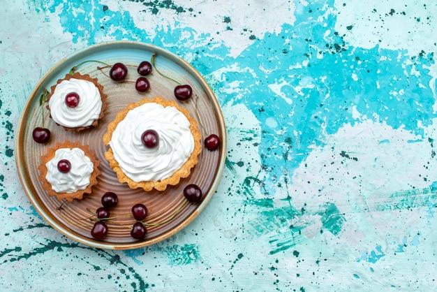 Vue de dessus de petits gâteaux aux cerises fraîches et crème délicieuse