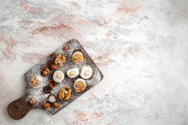 Vue de dessus de petits gâteaux aux noix et aux noisettes sur une surface blanche