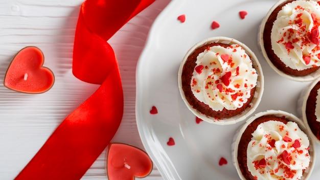 Vue de dessus de petits gâteaux avec des bougies en forme de coeur et ruban