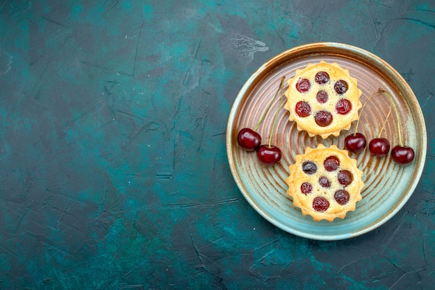Vue de dessus des petits gâteaux avec des cerises savoureuses sur bleu foncé,