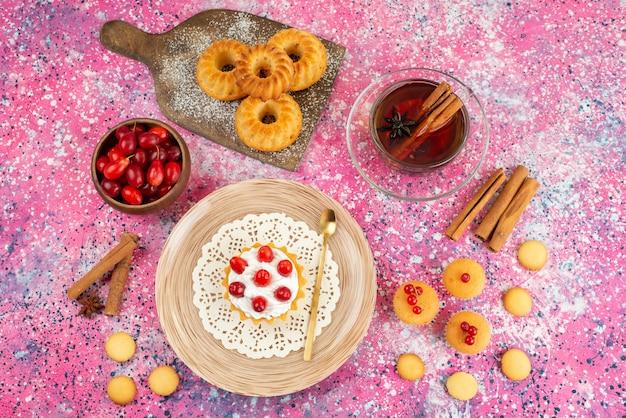 Vue de dessus petits gâteaux avec de la crème fraîche et des fruits frais avec de la cannelle et du thé sur le cookie lumineux de bureau
