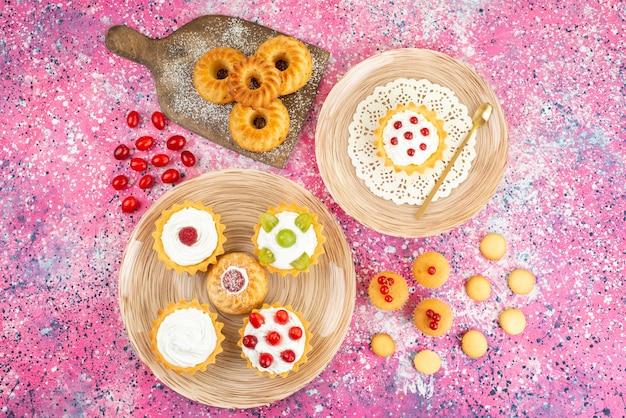 Vue de dessus petits gâteaux avec de la crème fraîche et des fruits sur la surface lumineuse gâteau sucré