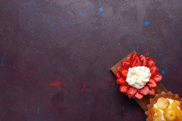 Vue de dessus de petits gâteaux crémeux avec des fruits tranchés sur une surface sombre