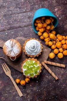 Vue de dessus de petits gâteaux délicieux avec des biscuits aux raisins tranchés à la crème et des cerises jaunes fraîches sur un bureau brun