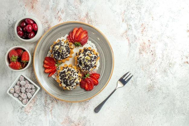 Vue de dessus de petits gâteaux délicieux avec de la crème et des fraises sur la surface blanche fête d'anniversaire gâteau aux biscuits sucrés