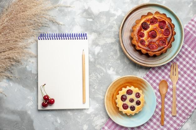 Vue de dessus de petits gâteaux délicieux et cuits au four avec des fruits sur la lumière, gâteau sucré au thé cuire au four tarte aux fruits