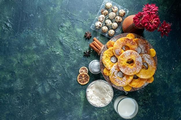 Vue de dessus de petits gâteaux délicieux en forme d'anneau d'ananas avec du lait sur fond sombre.