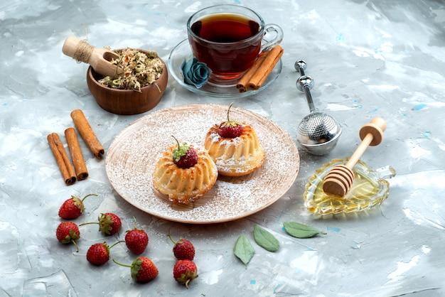 Une vue de dessus de petits gâteaux délicieux avec des fraises rouges, de la cannelle et des fruits gâteau au thé