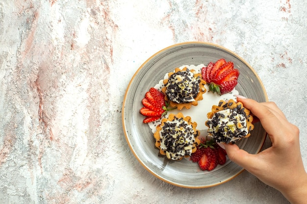 Vue de dessus de petits gâteaux délicieux avec des fraises sur une surface blanche fête d'anniversaire biscuit sucré gâteau biscuit