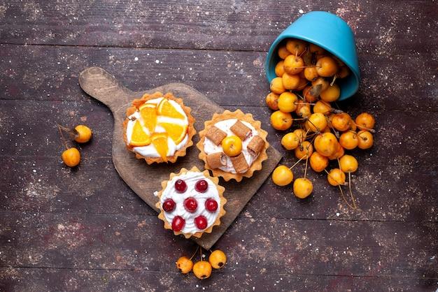 Vue de dessus de petits gâteaux délicieux avec des fruits tranchés à la crème et des cerises jaunes fraîches sur bois brun, biscuit gâteau aux fruits frais sucré