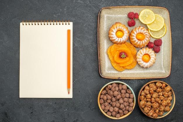 Vue de dessus de petits gâteaux délicieux avec des tranches de citron mandarines et bonbons sur gris