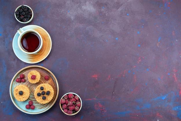 Vue de dessus de petits gâteaux sucrés et délicieux avec des baies fraîches et du thé sur la surface sombre