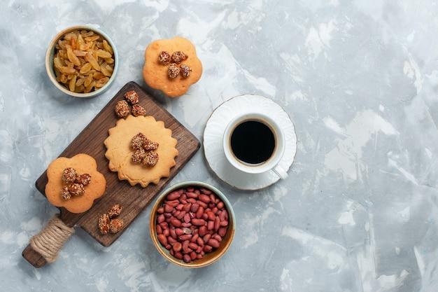 Vue de dessus de petits gâteaux avec thé aux pistaches et noix sur une surface blanche claire