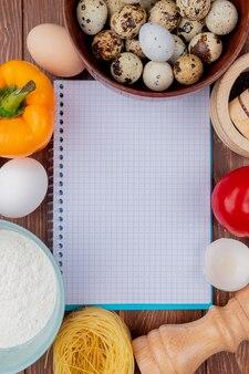 Vue de dessus de petits œufs de caille sur un bol en bois avec des œufs de poule blancs avec du poivron jaune à la tomate sur un fond en bois avec copie espace