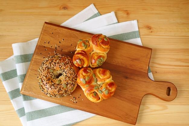 Vue de dessus de petits pains assortis sur plateau en bois servi sur table en bois