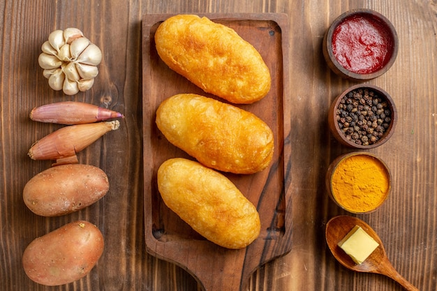 Vue de dessus des petits pains aux pommes de terre au four avec des assaisonnements sur un bureau en bois marron