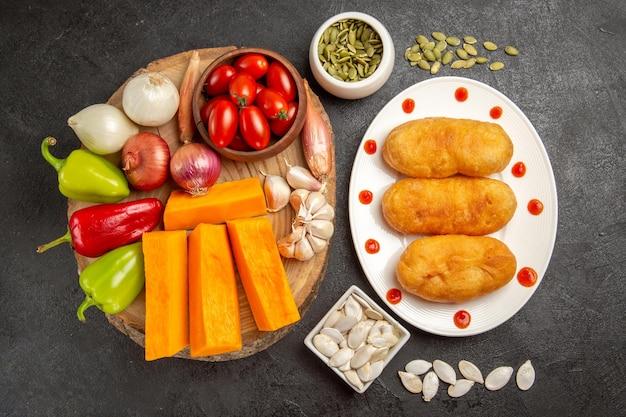 Vue de dessus des petits pains aux pommes de terre à l'intérieur de la plaque avec des légumes sur fond gris foncé tarte au four gâteau au four