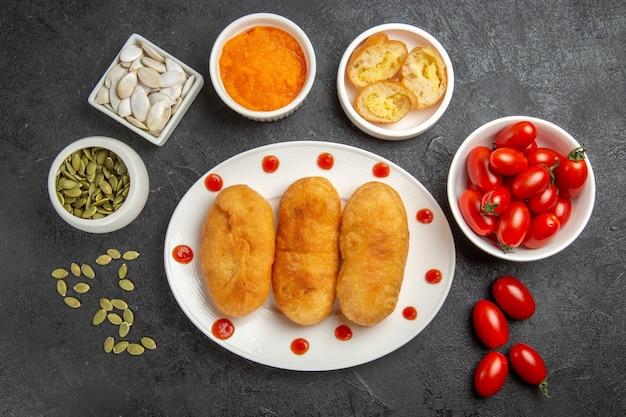 Vue de dessus des petits pains aux pommes de terre avec de petites tomates fraîches sur fond gris foncé tarte au four gâteau au four