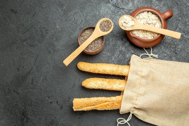 Vue de dessus des petits pains avec des céréales crues sur une surface grise