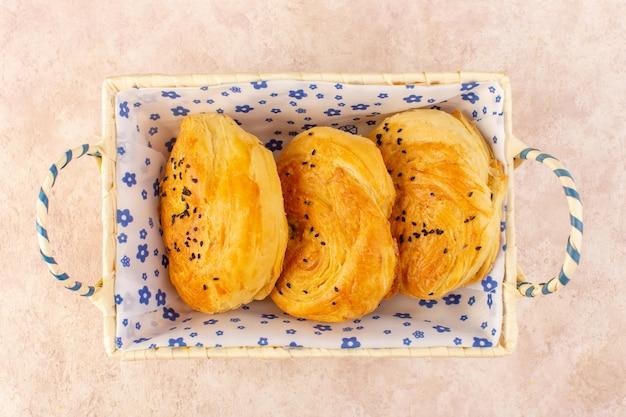 Une vue de dessus des petits pains chauds savoureux frais à l'intérieur du bac à pain sur rose