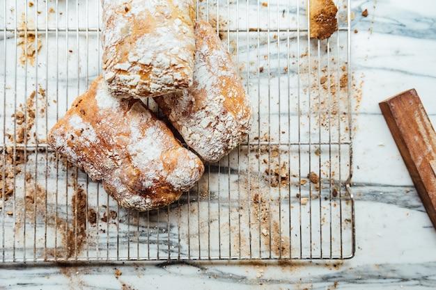 Vue de dessus des petits pains cuits au four fraîchement et chauds, placés sur le comptoir supérieur en marbre, à vendre.
