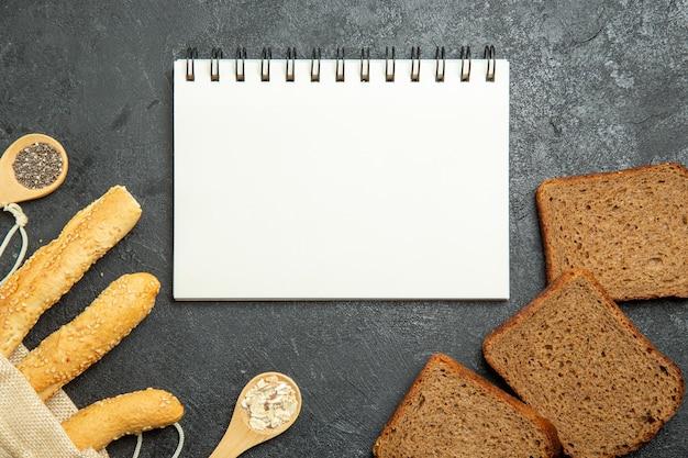 Vue de dessus des petits pains avec des miches de pain noir sur une surface gris foncé