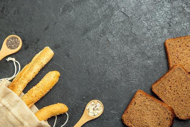 Vue de dessus des petits pains avec des miches de pain noir sur surface grise