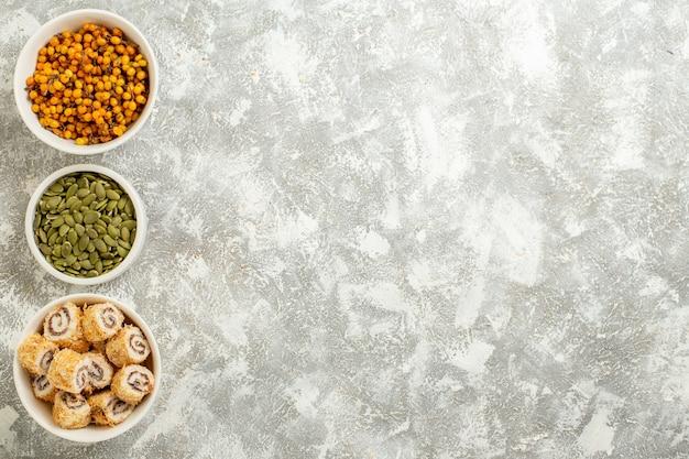 Vue de dessus des petits pains sucrés avec des graines sur fond blanc