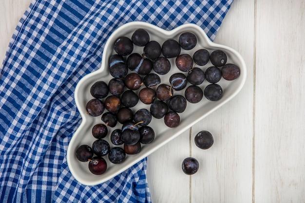Vue de dessus des petits prunelles bleu-noir aigre sur un bol blanc sur une nappe à carreaux bleu sur un fond de bois gris