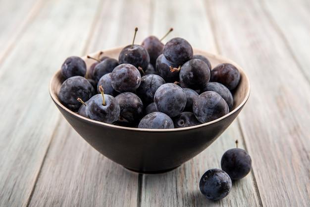 Vue de dessus des petits prunelles bleu-noir aigre sur un bol noir sur un fond en bois gris