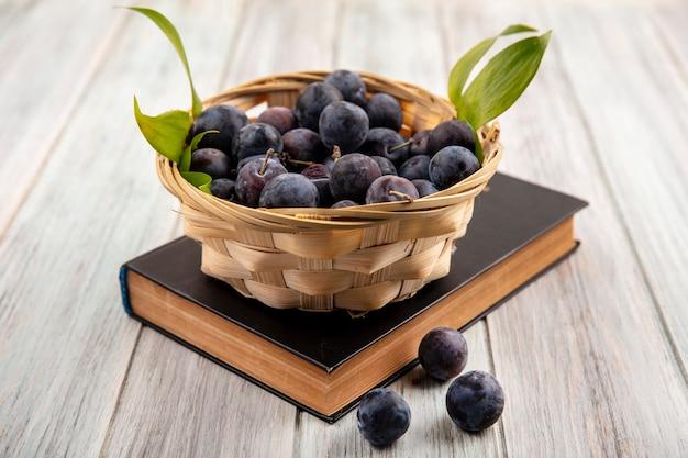 Vue de dessus des petits prunelles bleu-noir sauvage amer sur un seau avec des feuilles vertes sur un fond en bois gris