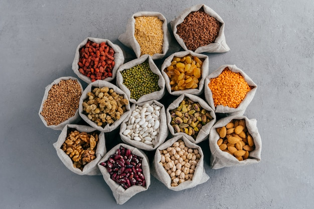 Vue de dessus de petits sacs avec des céréales: sarrasin, lentille, haricot, pois chiche, goji, raisins secs, pistache