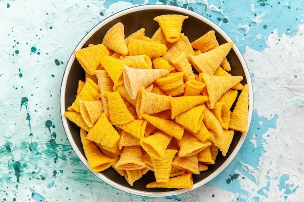 Vue de dessus peu de chips épicées à l'intérieur de la plaque sur la surface bleu clair chips snack couleur croustillant