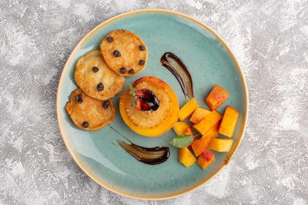 Vue de dessus peu de pâtisseries cookie à l'intérieur de la plaque avec des pêches en tranches fraîches sur table lumineuse, gâteau biscuit pâtisserie au sucre cuire