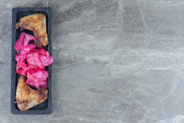 Vue de dessus pf aile de poulet grillé et chou mariné sur planche de bois.