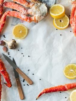 Vue de dessus des phalanges de crabe frais au citron et aux épices sur papier froissé.