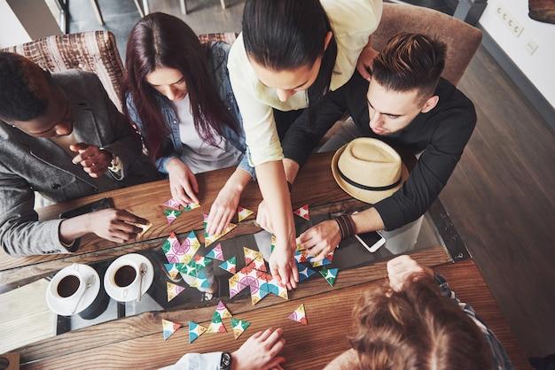 Vue de dessus photo créative d'amis assis à table en bois. amis s'amusant en jouant à un jeu de société