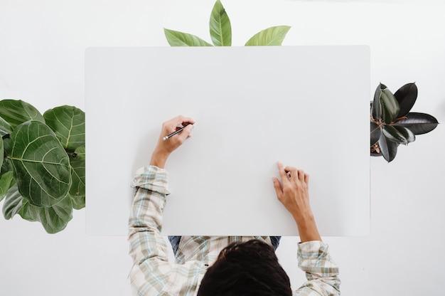 Vue de dessus des photos. un homme avec un crayon écrit sur un fond blanc avec un arbre autour.