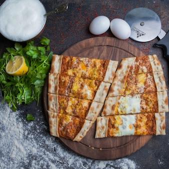 Vue de dessus pide avec viande hachée et œufs et ayran et couteau à pizza dans un plateau en bois