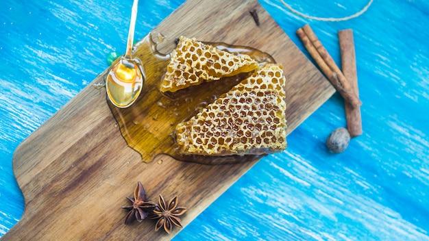 Une vue de dessus de pièces en nid d'abeille et d'épices sur fond texturé bleu