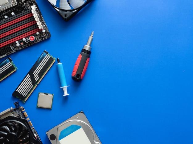 Vue de dessus des pièces d'ordinateur avec disque dur, ram, cpu, carte graphique et carte mère sur fond de tableau bleu.