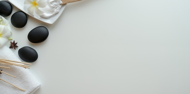 Vue de dessus de pierres noires et accessoires pour massages sur blanc