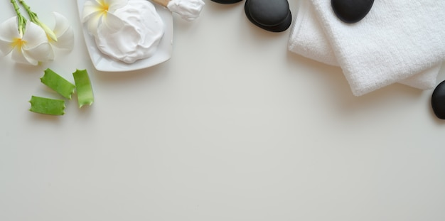Vue de dessus des pierres noires et des serviettes pour les massages sur blanc