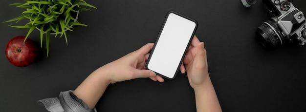 Vue de dessus de pigiste travaillant sur une maquette de smartphone sur tableau noir
